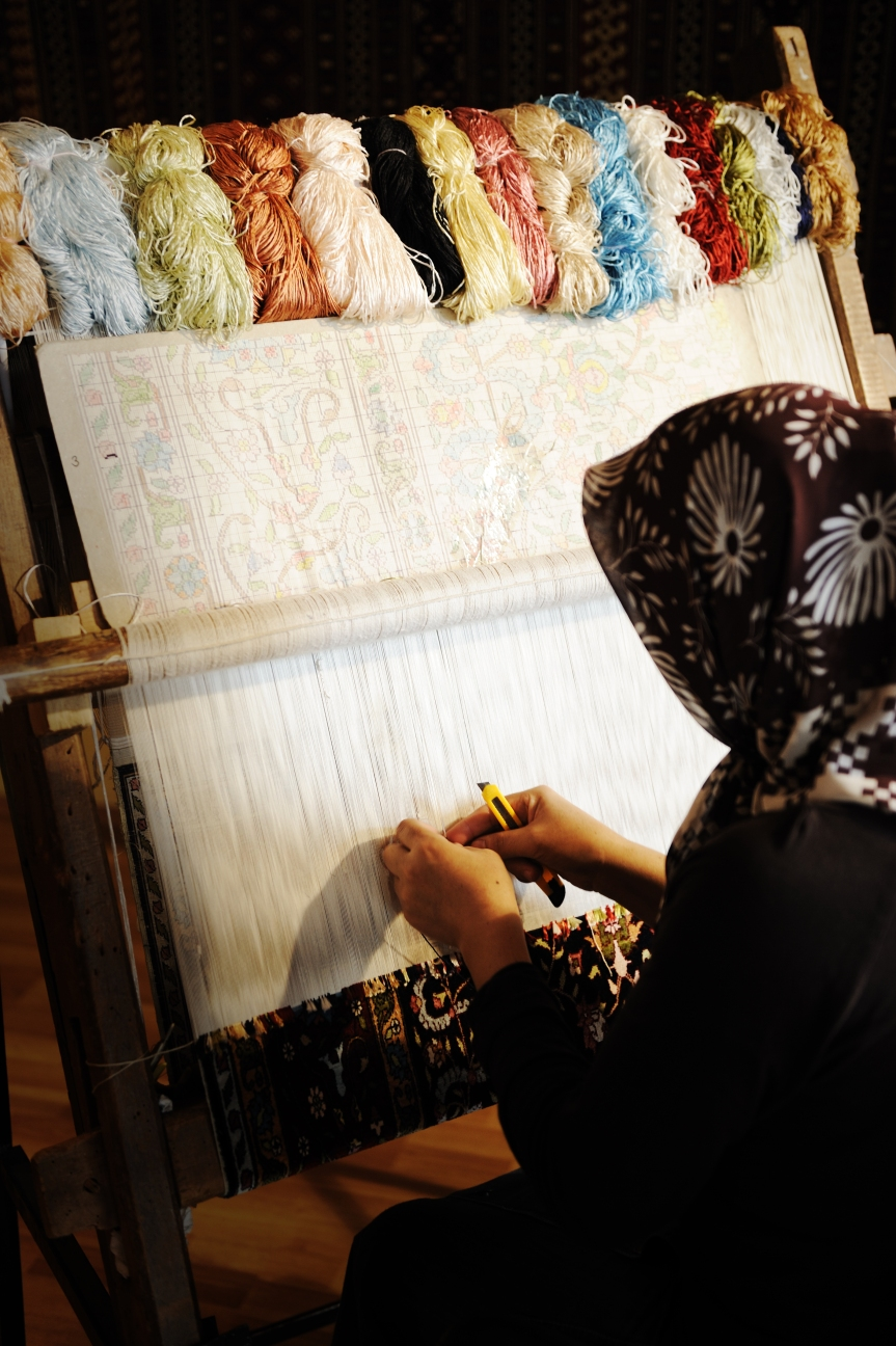 Woman working at the loom. Oriental Muslim national crafts. Focus on the fabric.
